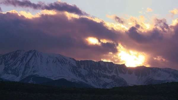 Timelapse of the snow-capped Sierra Nevada mountains with the sun shining through clouds. Royalty-free stock video