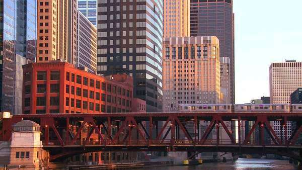 The El train travels over a bridge in front of the Chicago skyline. Royalty-free stock video