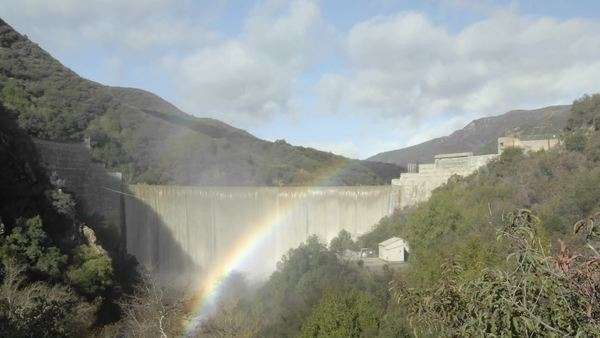 Wide timelapse of a rainbow moving across water spilling over the Matilija Dam after a rain in Ojai, California. Royalty-free stock video