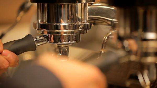 Barista connects the portafilter to an espresso machine and pulls a shot Royalty-free stock video