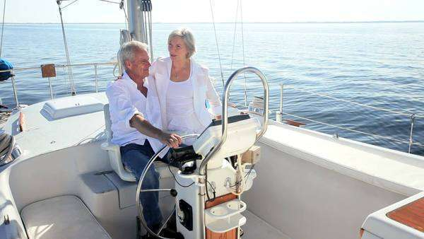 Healthy retired couple steering a course aboard their luxury sailing boat Royalty-free stock video