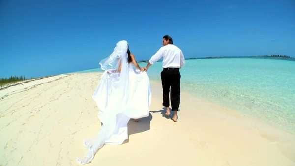 Barefoot Caucasian wedding couple enjoying time alone on a tropical beach Royalty-free stock video