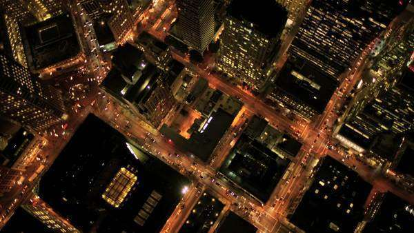 Aerial night vertical view of skyscraper rooftops and illuminated streets in a modern city Royalty-free stock video