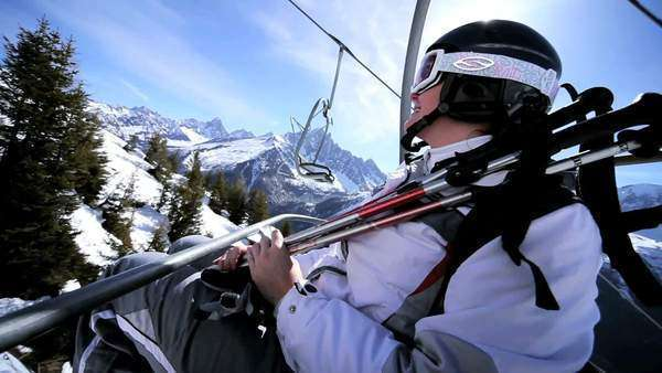 Skier travelling on ski lift to mountain top in winter Royalty-free stock video