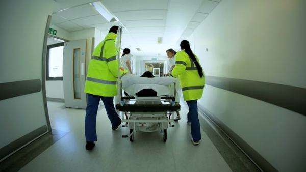 Emergency services wearing high visibility jackets medical staff pushing patient hospital bed along corridors to receive urgent treatment wide angle Royalty-free stock video