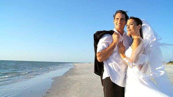 Bride & bridegroom on the beach after their wedding ceremony in close-up filmed at 60FPS Royalty-free stock video