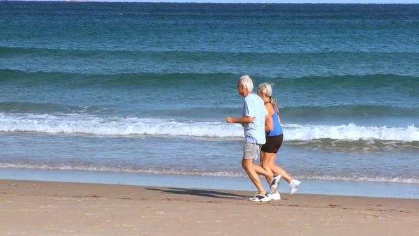 Healthy senior couple in sportswear keeping fit in their retirement jogging on the beach filmed at 60FPS Royalty-free stock video