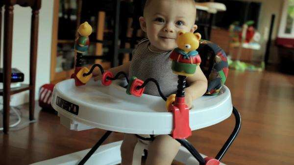 Excited baby moving around home in rolling chair. Royalty-free stock video