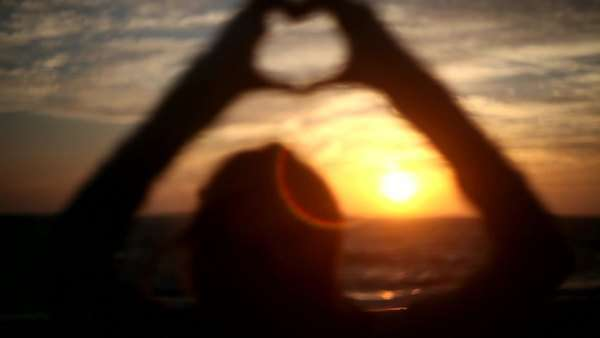 Soft focus on silhouette of hands making heart-shape in sky Royalty-free stock video