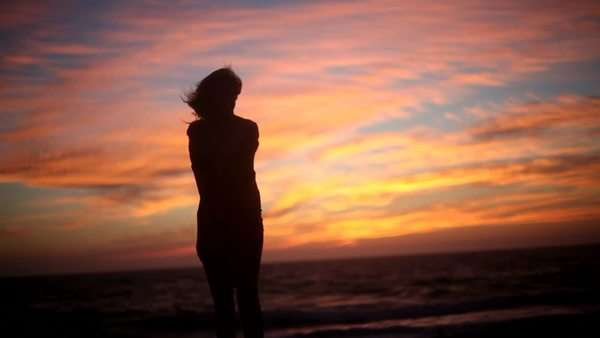 Silhouette of woman walking on beach against amazing sunset Royalty-free stock video