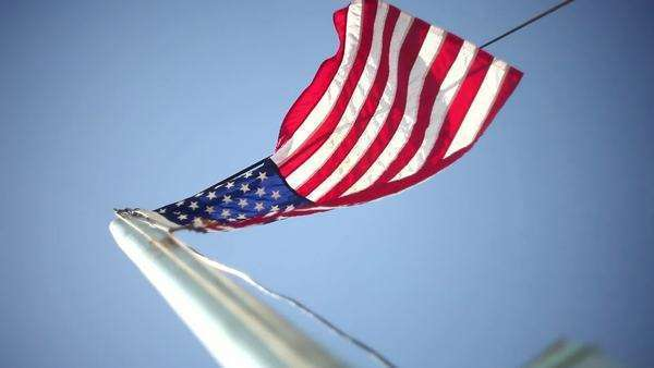 Changing focus on American flag blowing in wind Royalty-free stock video