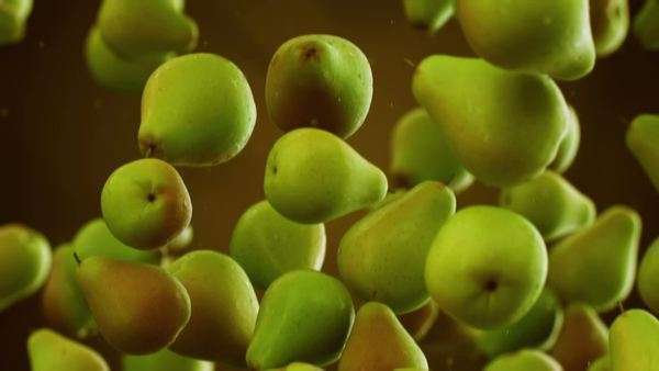 Slow motion CG animation of pears with water droplets falling down in front of blurry background Royalty-free stock video