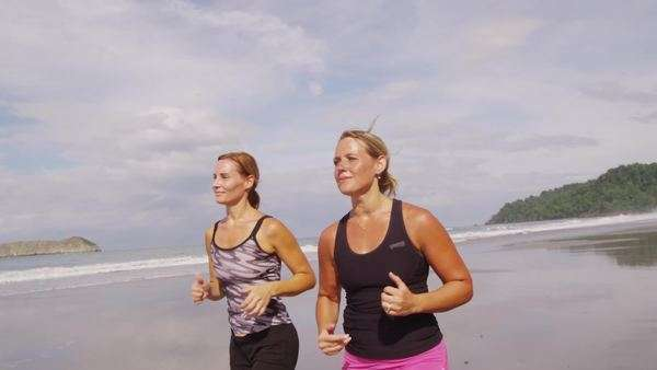 Two women running together on beach Royalty-free stock video
