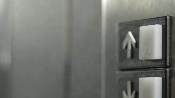 Manicured finger presses the button for an elevator but it doesn't light up, so they press it again and again.  Dolly shot. Royalty-free stock video
