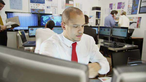 Young and ambitious male stock market trader hard at work in a busy office Royalty-free stock video
