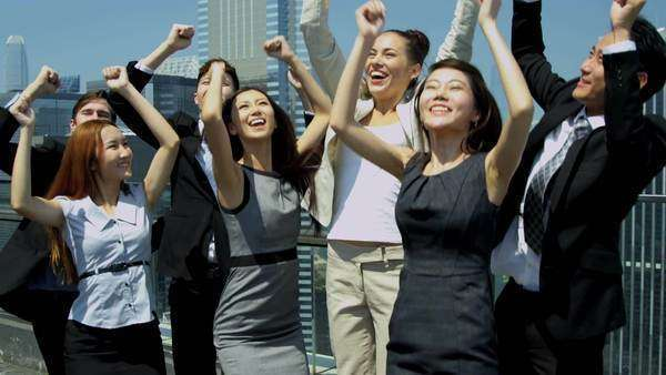 Portrait of triumphant team Asian Chinese Caucasian corporate business partners jumping joy office rooftop downtown city shot on RED EPIC Royalty-free stock video