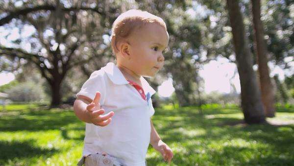 Cute little Caucasian male toddler child gaining confidence walking by himself sunny afternoon park slow motion shot on RED EPIC Royalty-free stock video