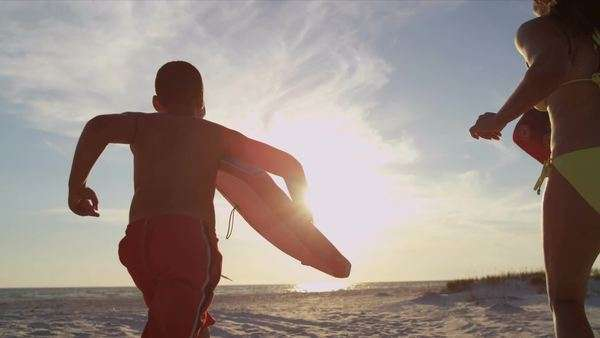 Healthy African American family summer vacation running across sand beach with bodyboards surfboards slow motion shot on RED EPIC Royalty-free stock video