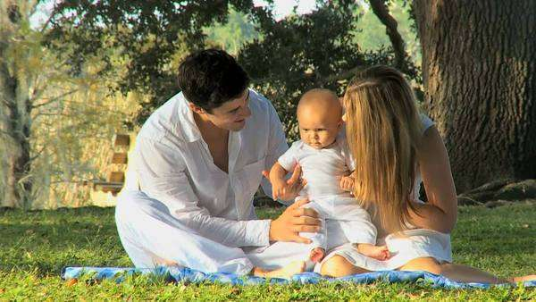 Young Caucasian parents sitting outdoors on the grass spending time with  their young baby girl Royalty-free stock video