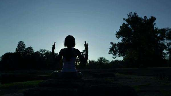 Silhouette of sitting black woman doing yoga Royalty-free stock video