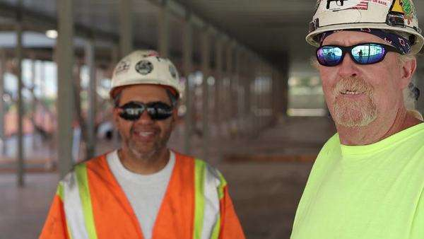 Construction workers wearing sunglasses giving thumbs up with one worker in foreground Royalty-free stock video