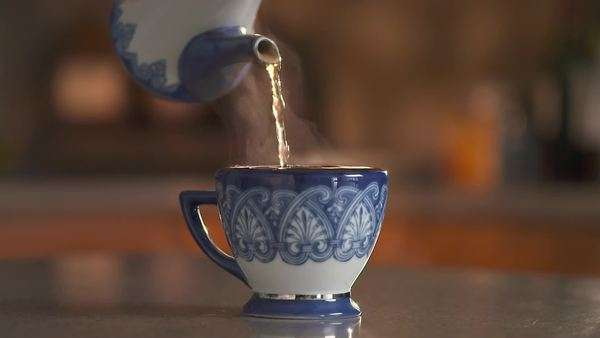 Steaming tea pouring into an overflowing cup Royalty-free stock video