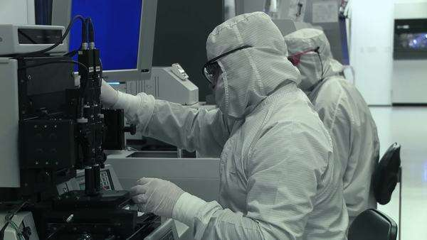 Two technicians working on silicon chip manufacture in a clean room, mid shot, locked off Royalty-free stock video