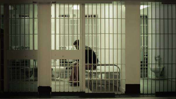 Inmate gets up from cot and stands at the bars in a prison cell Royalty-free stock video