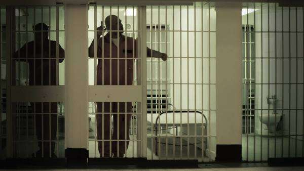 Inmate standing at the bars of his prison cell. Neighboring inmate can be seen in next cell Royalty-free stock video
