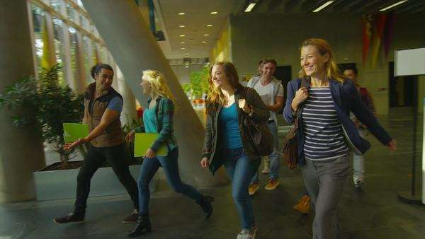 Cheerful student group leaving college building and walking out into the sunlight Royalty-free stock video