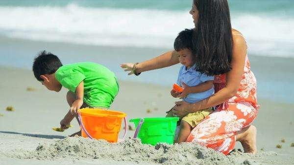 Little Latin American brothers playing together with young mother on beach shot on RED EPIC. Royalty-free stock video