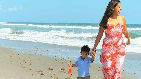 Young Latin American mother walking ocean shallows cute little boy holding plastic spade. Royalty-free stock video