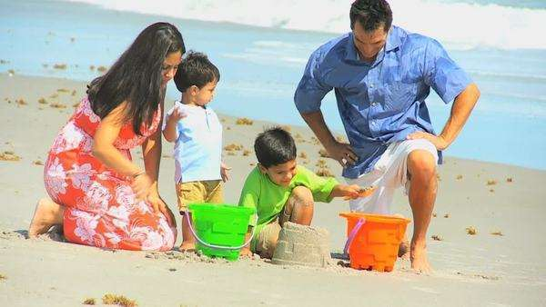Cute little ethnic brothers beach buckets with young Hispanic parents wearing bright casual clothing. Royalty-free stock video