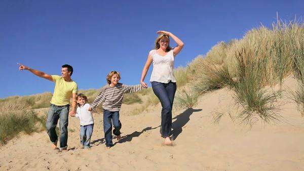 Attractive healthy young caucasian family having fun together on coastal sand dunes. Royalty-free stock video