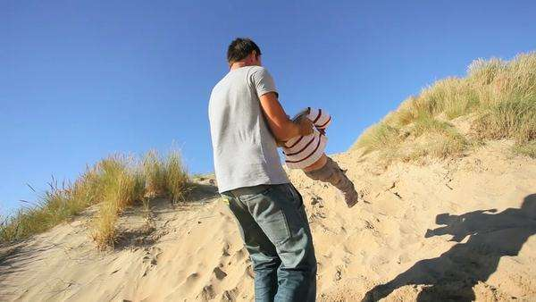 Young Caucasian father with his young son playing together in sand dunes by the coast. Royalty-free stock video
