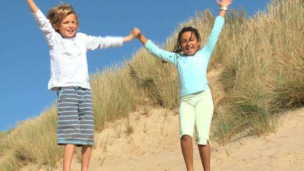 Mixed race childhood friends having fun playing in sand dunes by the coast. Royalty-free stock video