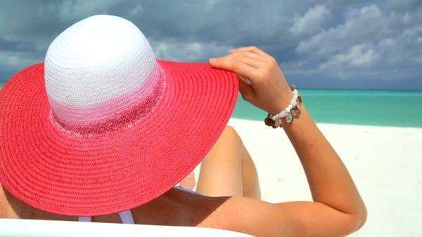 A woman with a pink straw hat surveys an ocean horizon from a tropical beach. Royalty-free stock video