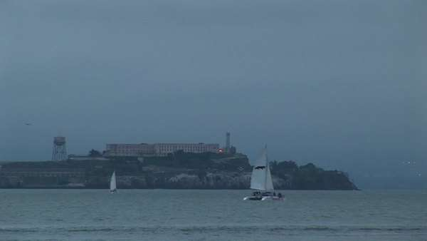A catamaran glides by historic Alcatraz Prison on a foggy day. Royalty-free stock video