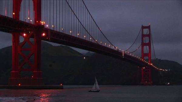 A worms-eye view of the Golden Gate Bridge at night with its lights reflecting on the water. Royalty-free stock video