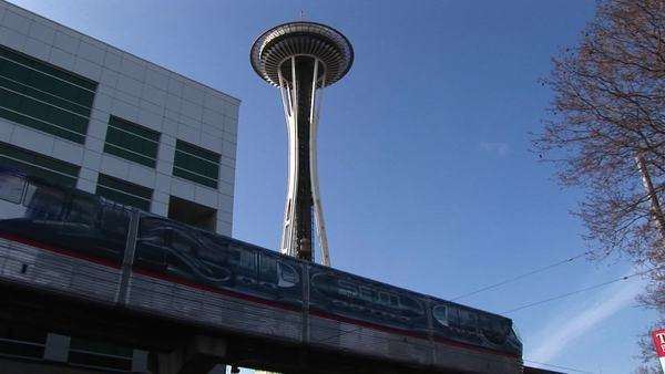 A close-up of the monorail passing by Seattle's landmark Space Needle. Royalty-free stock video