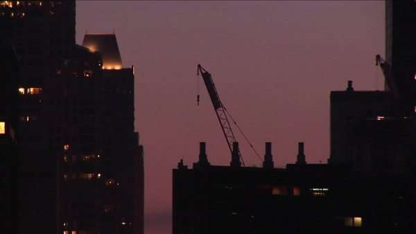 A building crane rests on a rooftop in a golden-hour skyline shot. Royalty-free stock video