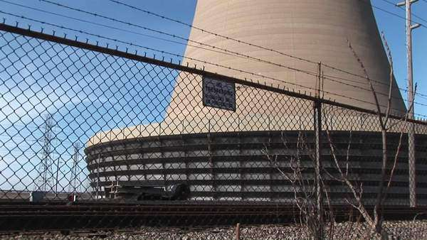 The camera pans from the base of a nuclear power plant to the top of its curved structure. Royalty-free stock video