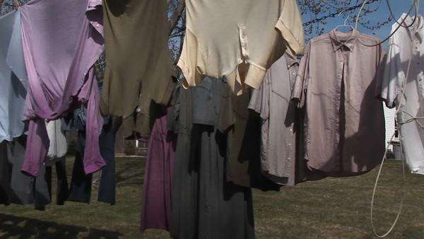 Colorful shirts and dark dresses hand on a clothesline to dry near a large country home. Royalty-free stock video