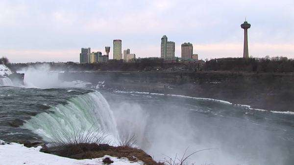 The tourist hotels and viewing tower look stark against a pale sky with Niagara Falls in the foreground. Royalty-free stock video