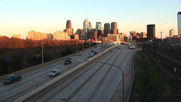Philadelphia glows during the golden-hour as traffic enters and departs the city via a divided expressway. Royalty-free stock video