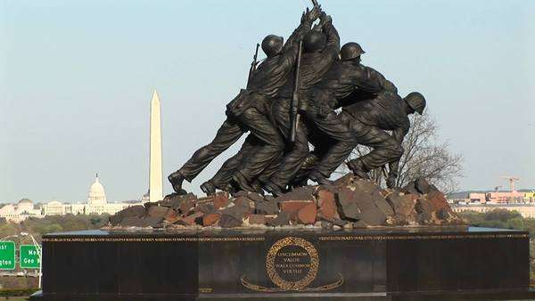 The camera slowly pans-up the Iwo Jima Marine Corps memorial to the American flag. Royalty-free stock video