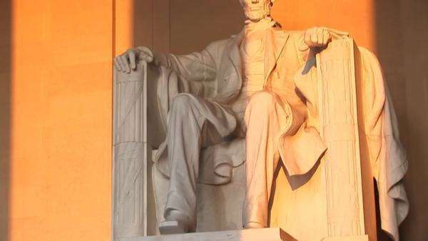 Columns of the Lincoln Memorial Building cast long shadows on the statue of Abraham Lincoln. Royalty-free stock video