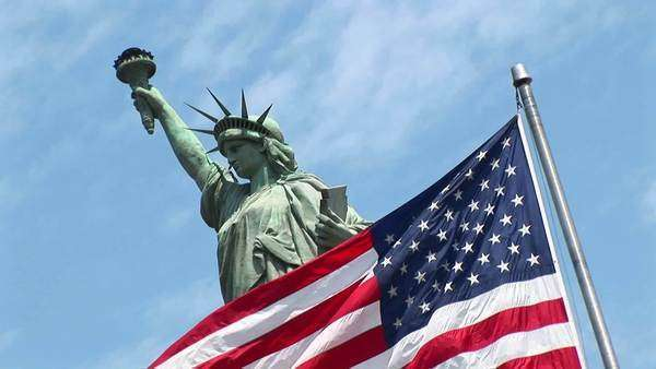An American flag waves in front of The Statue of Liberty. Royalty-free stock video