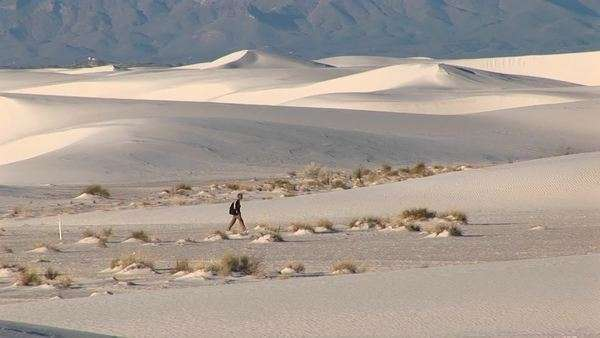 Long-shot of a hiker walking through White Sands National Monument in New Mexico. Royalty-free stock video