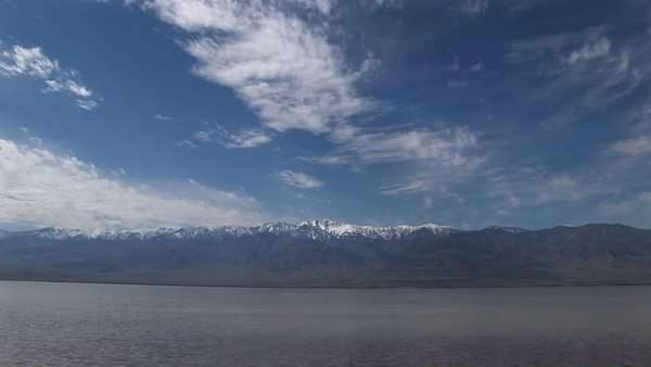 Long-shot of the Badwater Lake with the Owlshead Mountains on the horizon in Death Valley National Park. Royalty-free stock video